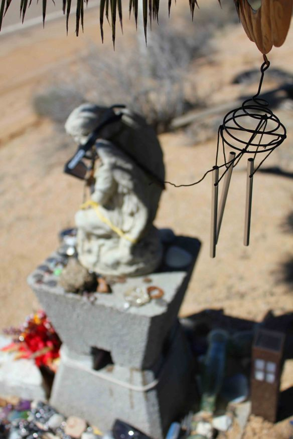 A wind chime hangs from the massive Joshua Tree.